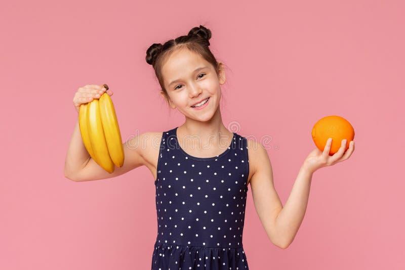 Fille gaie mignonne tenant les bananes fra?ches et le fruit orange photo stock
