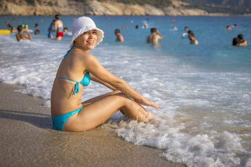 Fille gaie s'asseyant sur la plage dans Oludeniz, Turquie photographie stock