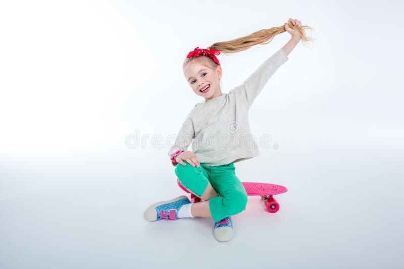 Fille gaie s'asseyant sur la planche à roulettes sur le gris images stock