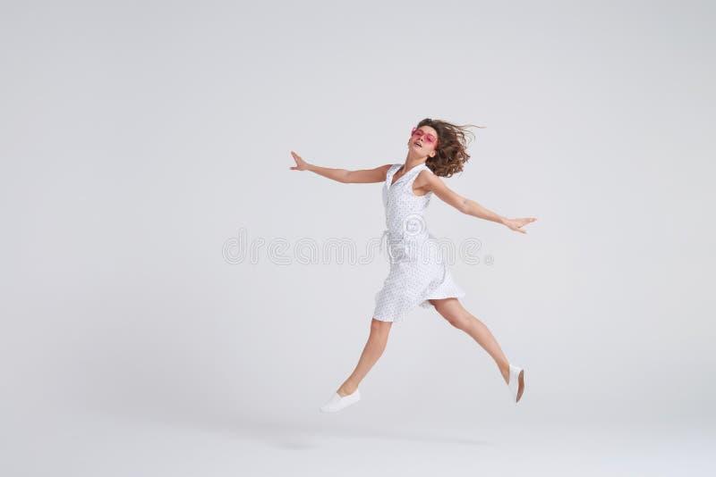 Fille gaie sautant en air au-dessus du fond blanc image stock
