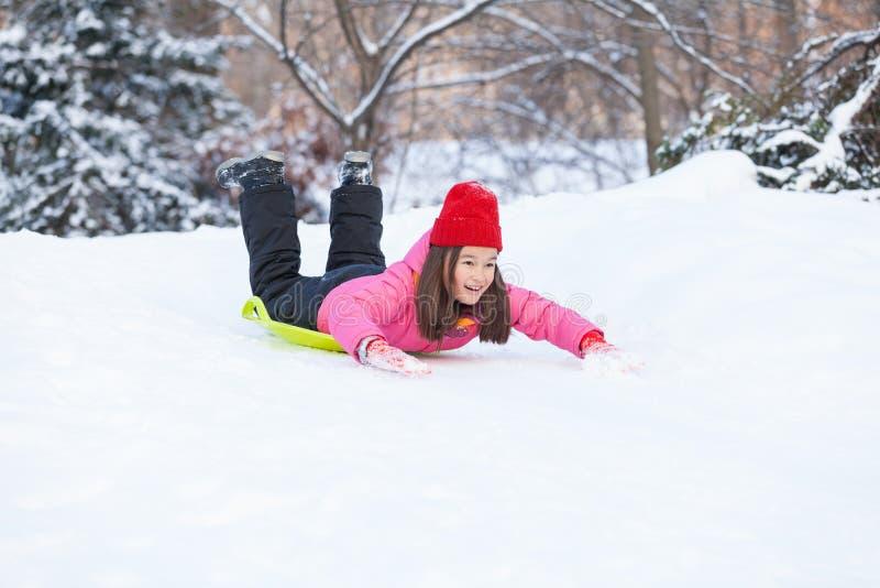 Fille glissant sur la neige de la colline rapidement images stock