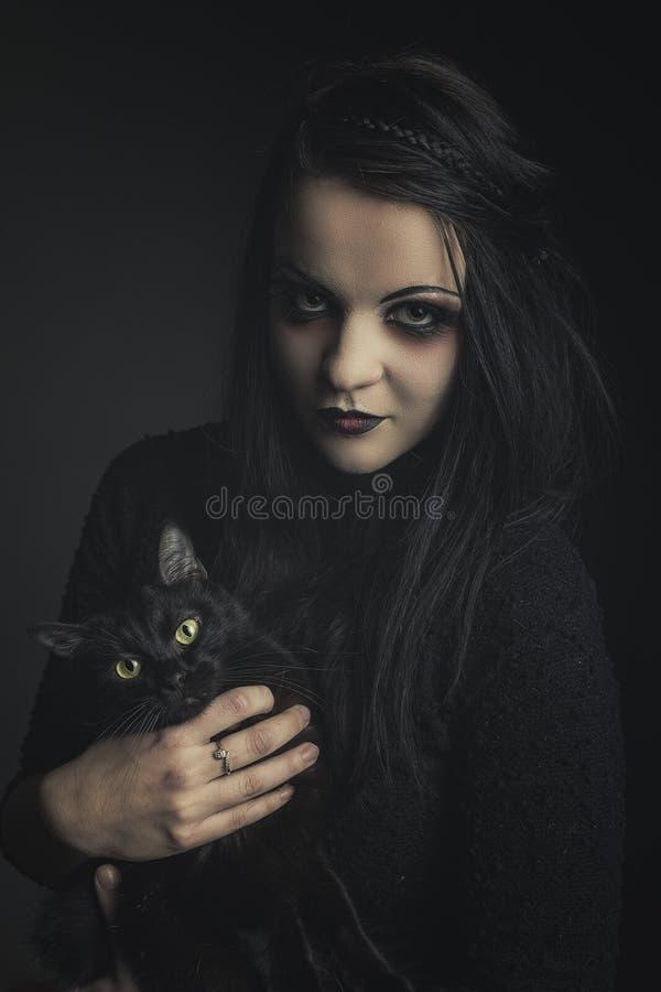 Fille gothique tenant un chat noir images libres de droits