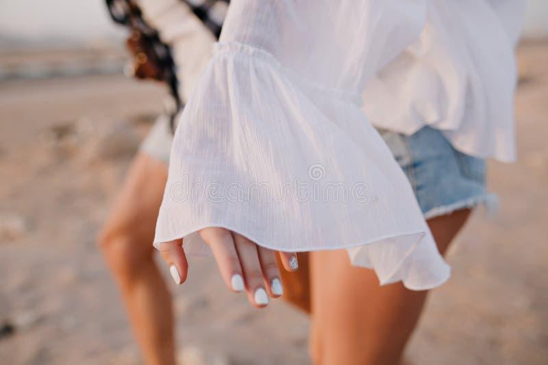 Fille gracieuse dans des shorts de chemisier et de denim de cru avec la manucure blanche ? la mode ayant l'amusement en dehors du photos stock