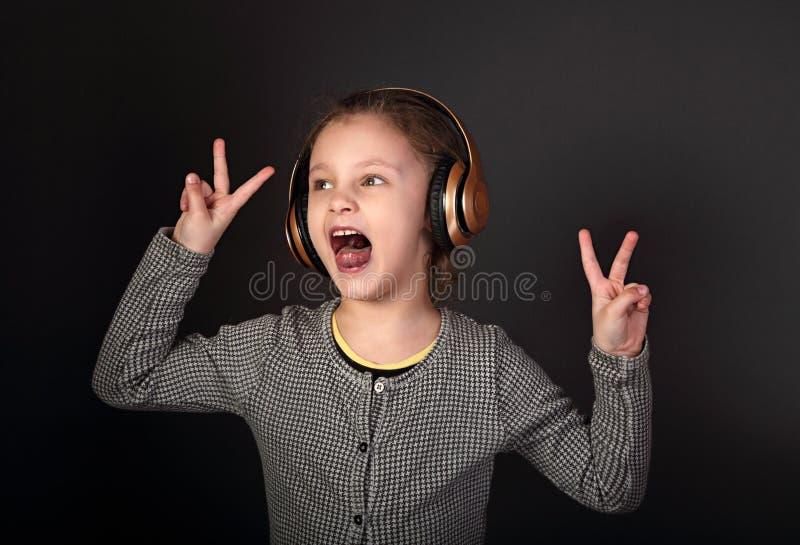 Fille grimaçante drôle d'enfant écoutant la musique, chantant dans les wireles images libres de droits