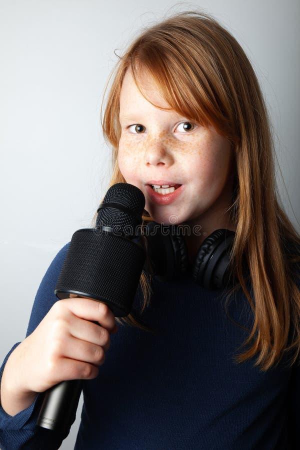 Fille grosse avec son microphone et ses sourires Portrait sur fond blanc photo libre de droits