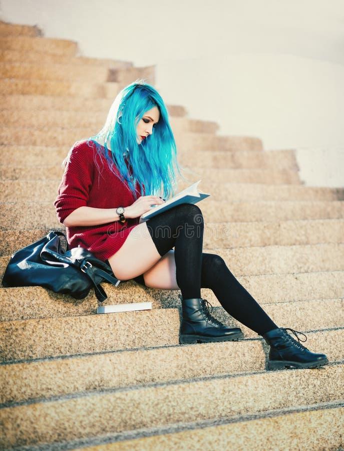Fille grunge aux cheveux bleus assez jeune s'asseyant sur des escaliers et lisant un livre photos libres de droits