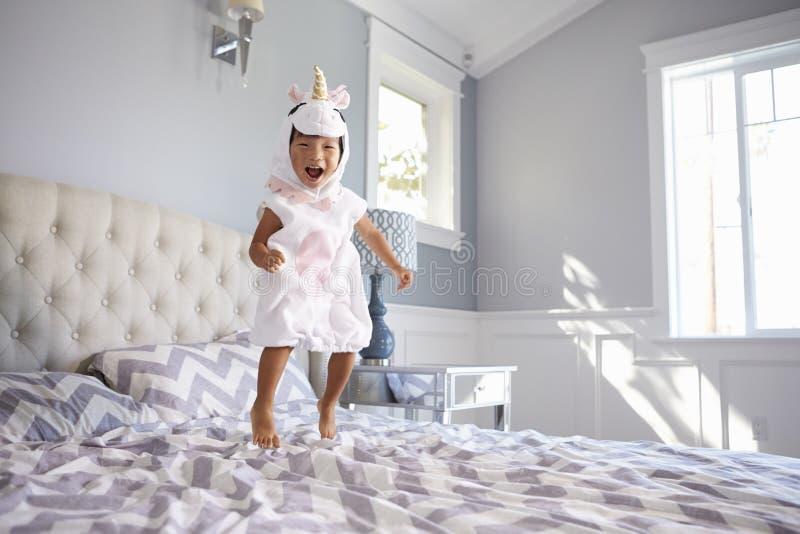 Fille habillée en Unicorn Costume Jumping On Bed à la maison images stock
