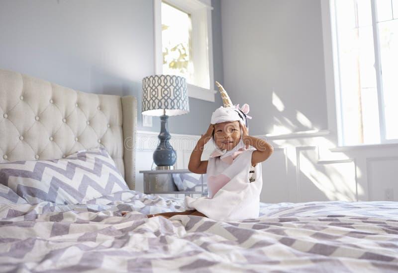Fille habillée en Unicorn Costume Sitting On Bed à la maison photographie stock