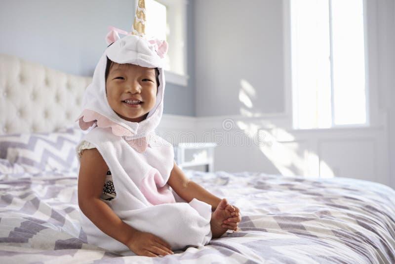 Fille habillée en Unicorn Costume Sitting On Bed à la maison image stock