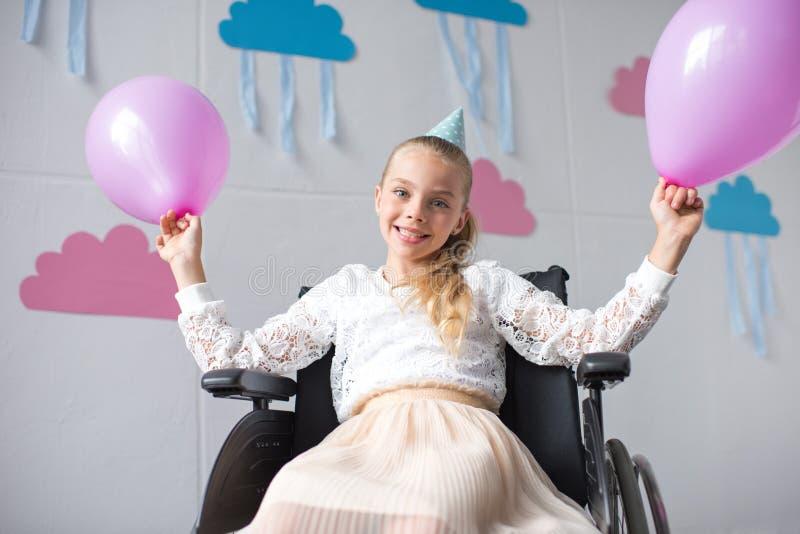 fille handicapée gaie tenant des ballons et souriant à l'appareil-photo photos stock