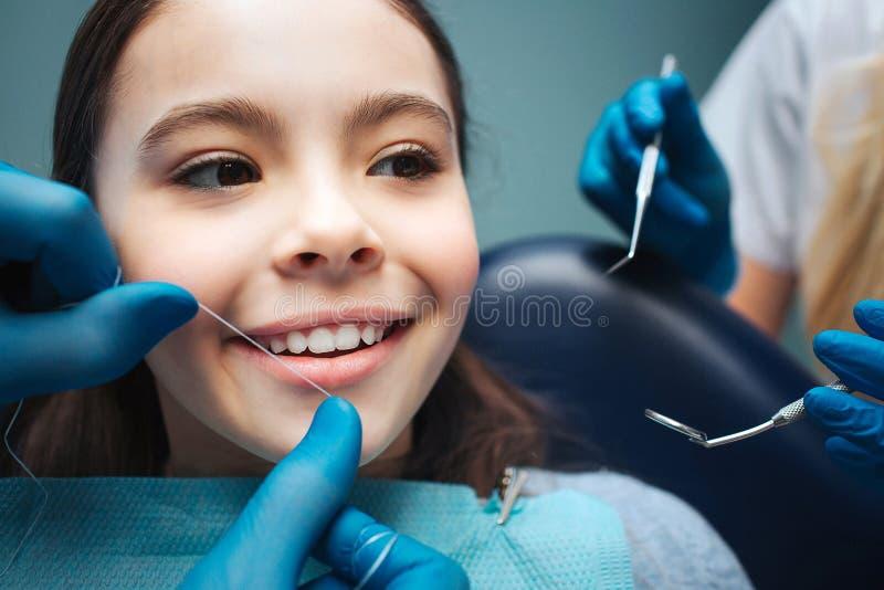 Fille haute étroite dans la chaise dentaire Main aux dents avant de soie Les mains de la femme tiennent des outils image libre de droits