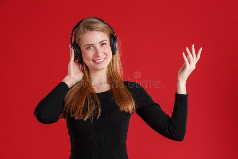 Fille heureuse, écoutant la musique dans des écouteurs et le sourire mignon Sur un fond rouge photographie stock libre de droits