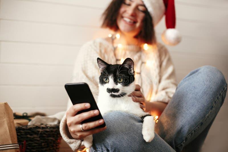 Fille heureuse élégante dans le chapeau de Santa avec le chat mignon regardant l'écran de téléphone sur le fond des lumières et d photographie stock libre de droits