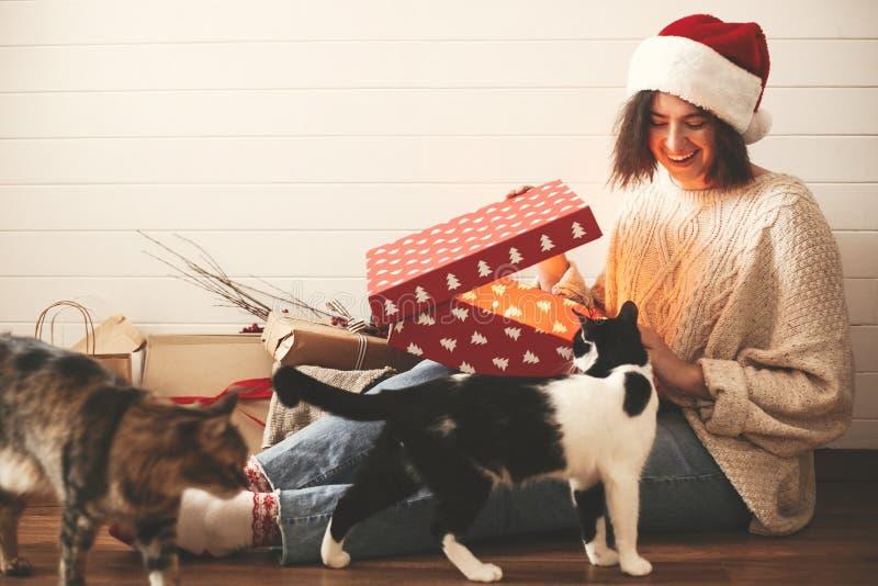 Fille heureuse élégante dans le chapeau de Santa et ses chats ouvrant le boîte-cadeau de Noël avec la lumière magique dans la piè images stock