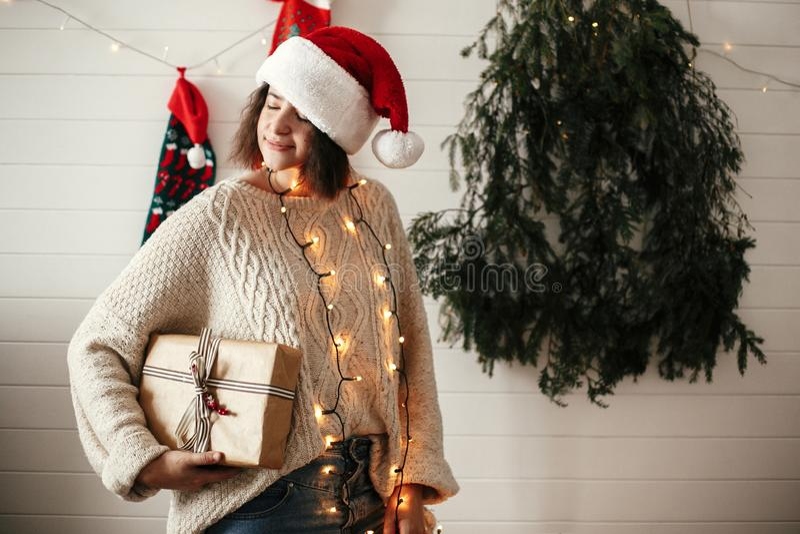 Fille heureuse élégante dans le chapeau de Santa tenant le boîte-cadeau de Noël sur le fond de l'arbre, des lumières et des bas m image libre de droits