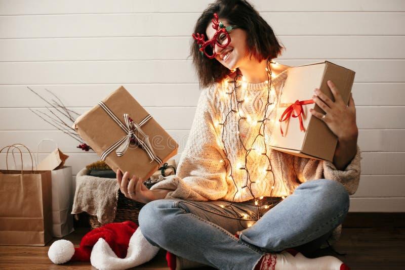 Fille heureuse élégante en verres de fête avec des klaxons de renne souriant et tenant des boîte-cadeau de Noël dans des lumières image libre de droits