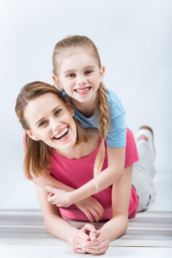 Fille heureuse étreignant la mère riante sur le blanc photo stock
