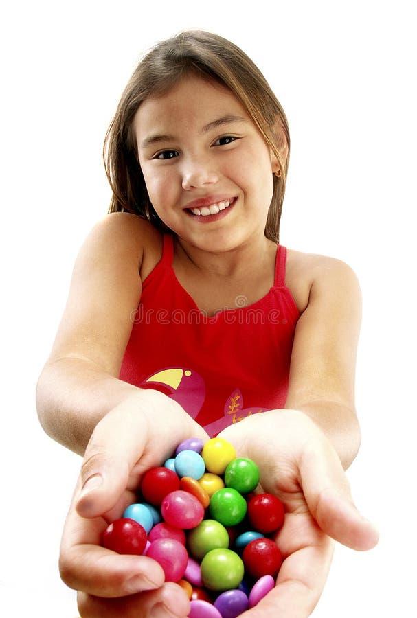 Fille heureuse affichant la sucrerie images libres de droits