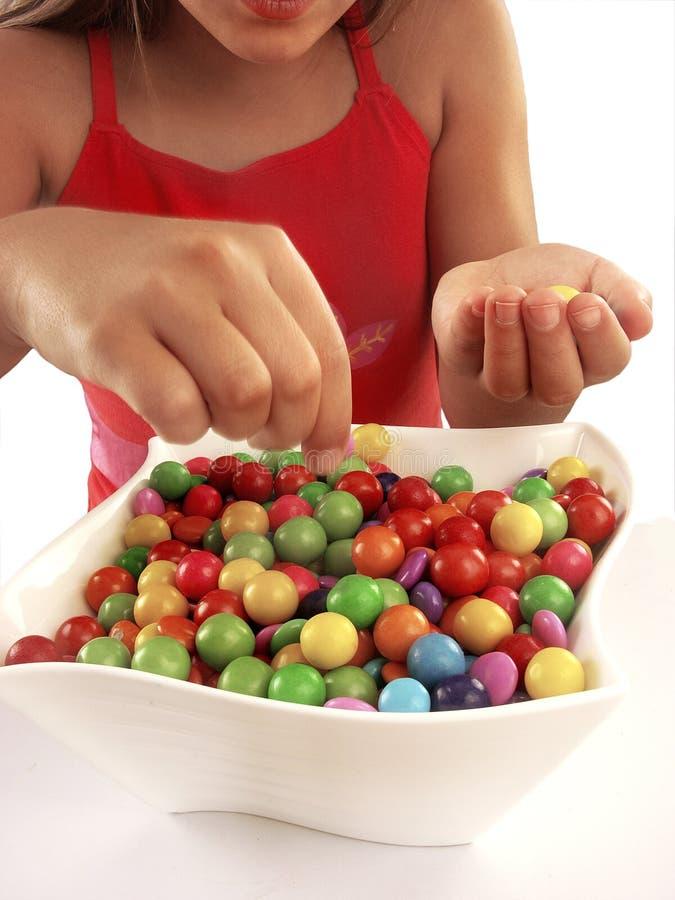 Fille heureuse affichant la sucrerie images stock