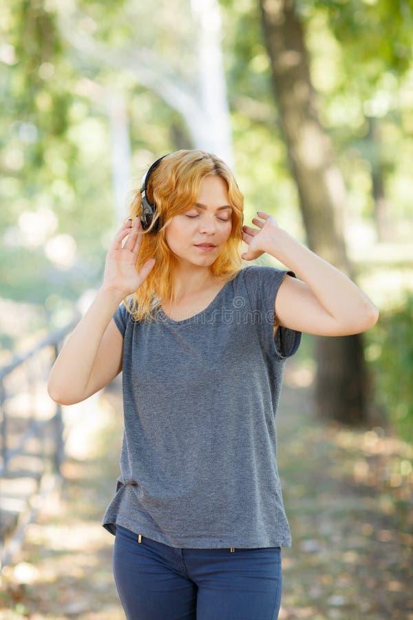 Fille heureuse appréciant la musique Belle femme dans des écouteurs sur un fond de parc Concept actif de style de vie photos libres de droits