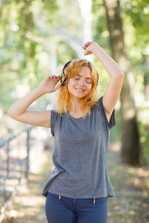 Fille heureuse appréciant la musique Belle femme dans des écouteurs sur un fond de parc Concept actif de style de vie image stock