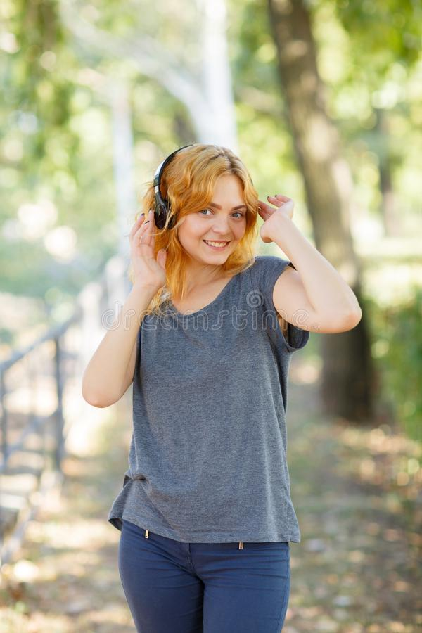 Fille heureuse appréciant la musique Belle femme dans des écouteurs sur un fond de parc Concept actif de style de vie photo libre de droits