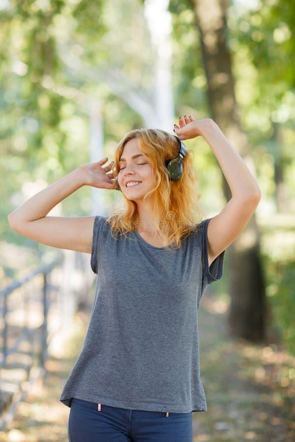 Fille heureuse appréciant la musique Belle femme dans des écouteurs sur un fond de parc Concept actif de style de vie photo stock