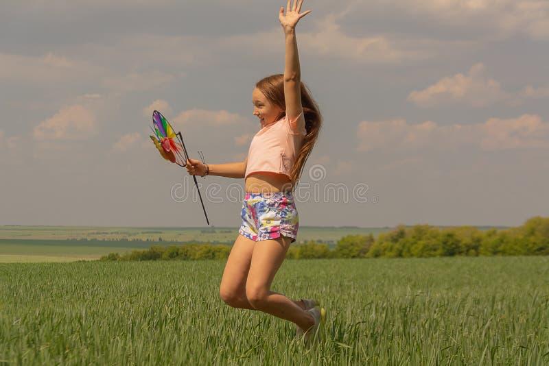 Fille heureuse avec de longs cheveux tenant un moulin à vent coloré et des sauts image libre de droits
