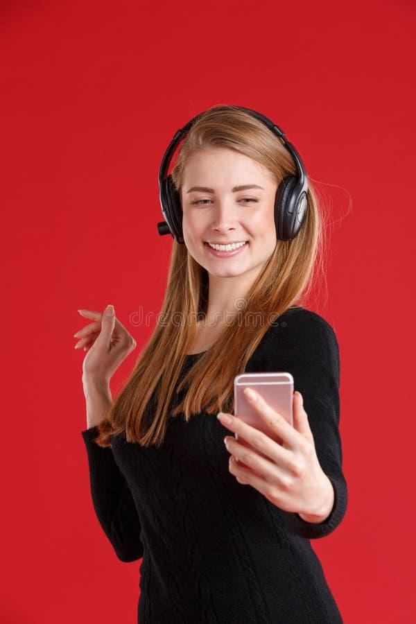 Fille heureuse avec des écouteurs, souriant et tenant le téléphone portable sur la main tendue Sur un fond rouge photographie stock libre de droits