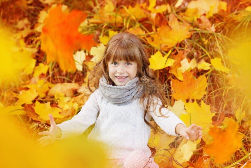 Fille heureuse avec des feuilles d'automne extérieures image stock