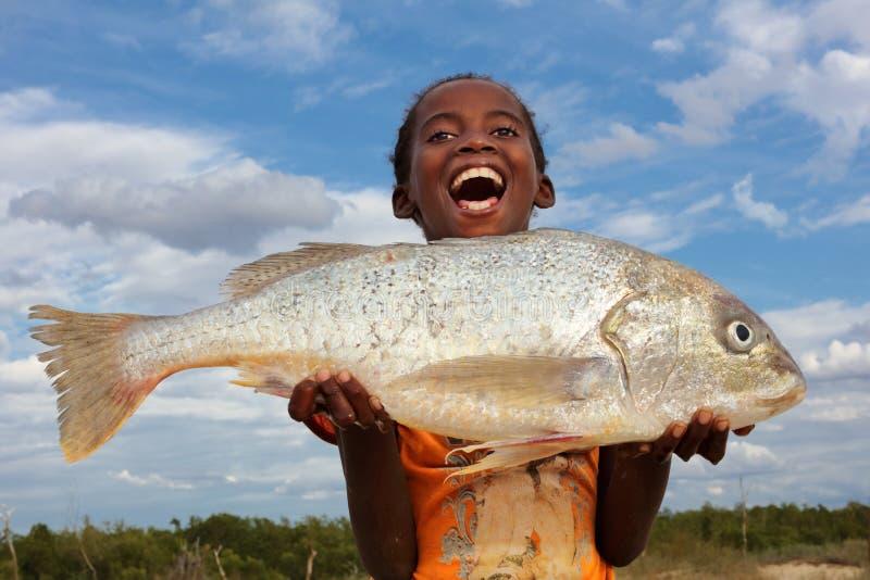 Fille heureuse avec des poissons, Madagascar image libre de droits