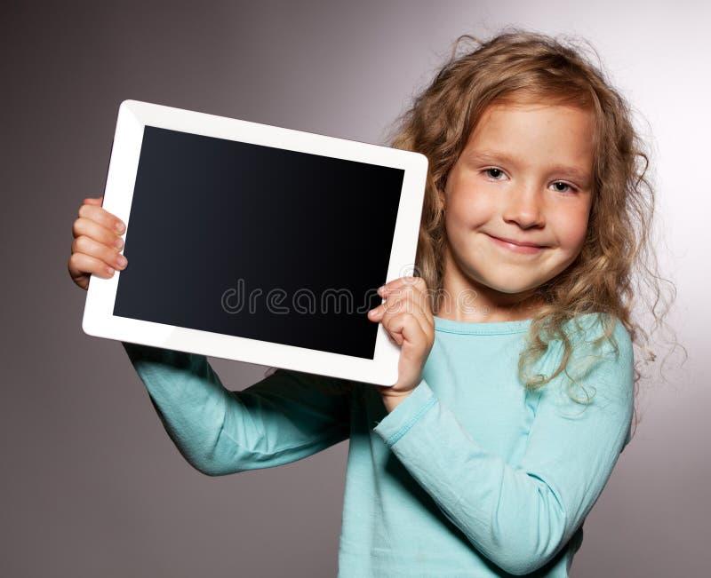 Fille heureuse avec l'ordinateur de tablette photographie stock libre de droits