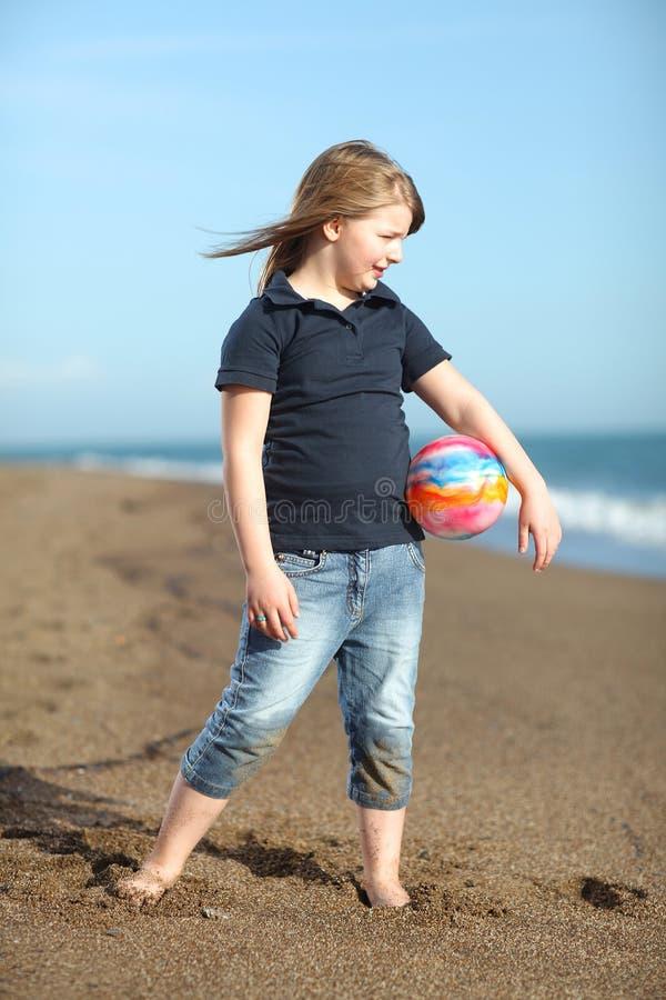 Fille heureuse avec la bille sur la plage photo libre de droits