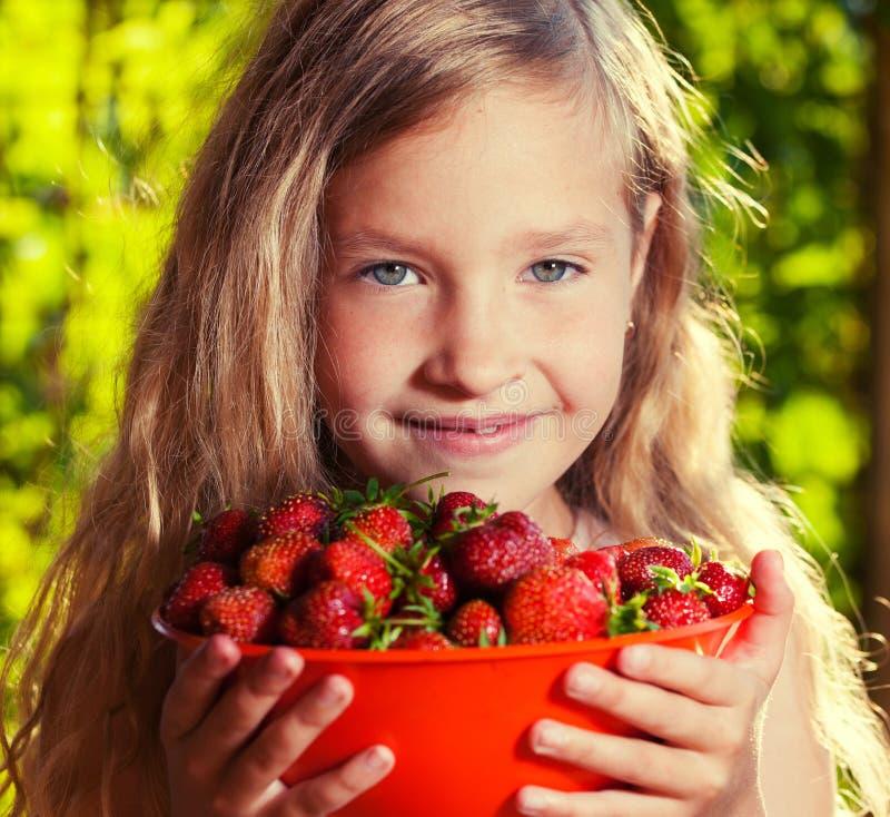 Fille heureuse avec la fraise photographie stock