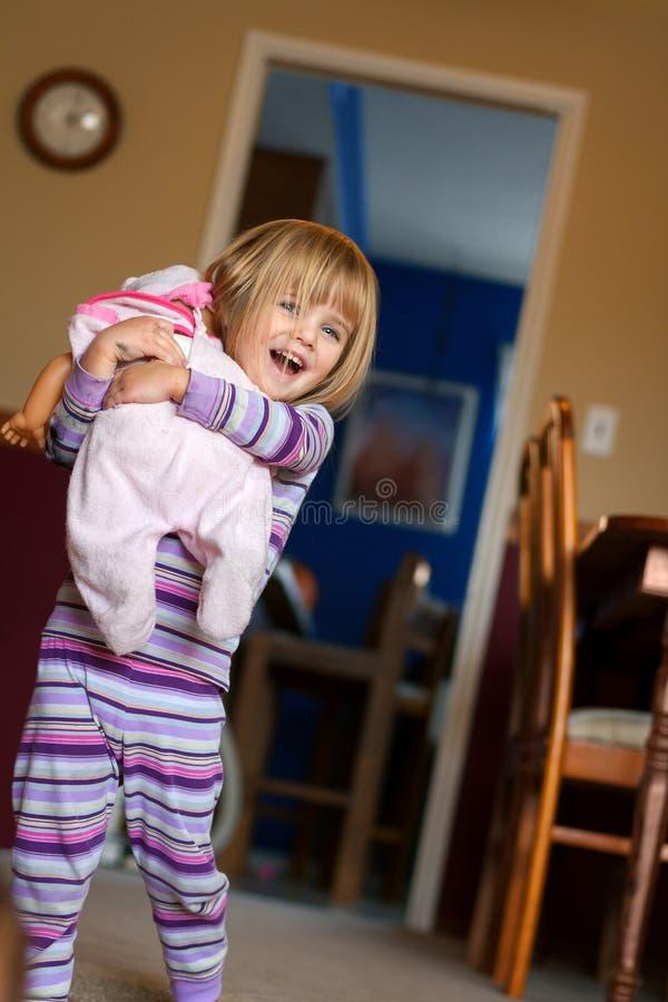 Fille heureuse avec la lumière naturelle de poupée photographie stock