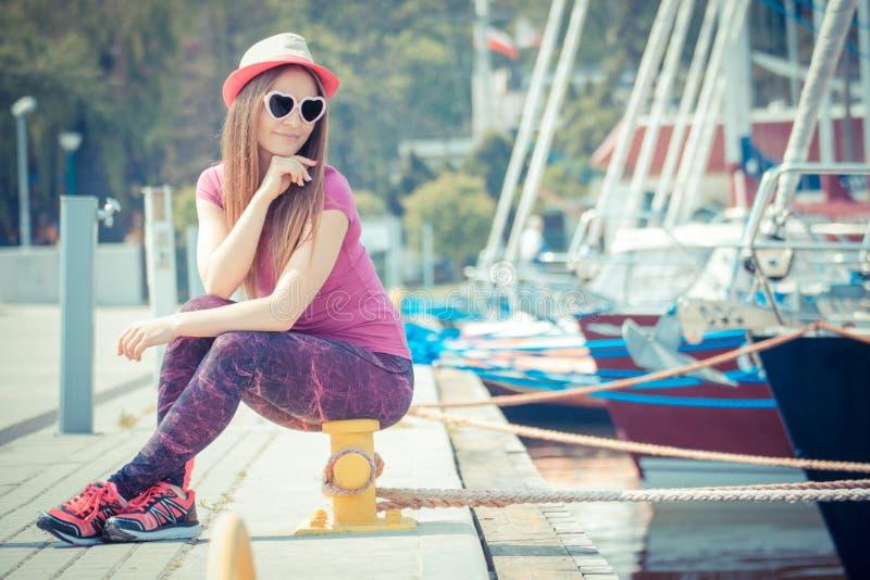 Fille heureuse avec le chapeau de paille et les lunettes de soleil dans le port avec le yacht à l'arrière-plan, heure d'été photos stock