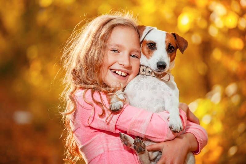 Fille heureuse avec le chien à l'automne images libres de droits