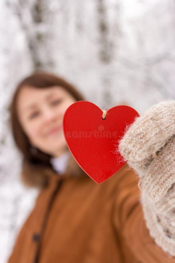Fille heureuse avec le coeur en bois rouge se tenant dans des mains à l'arrière-plan unfocused de forêt d'hiver Jour de valentine image stock