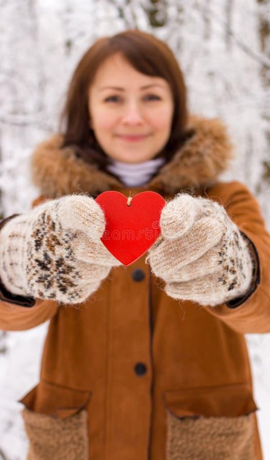 Fille heureuse avec le coeur en bois rouge se tenant dans des mains à l'arrière-plan unfocused de forêt d'hiver Jour de valentine photos libres de droits