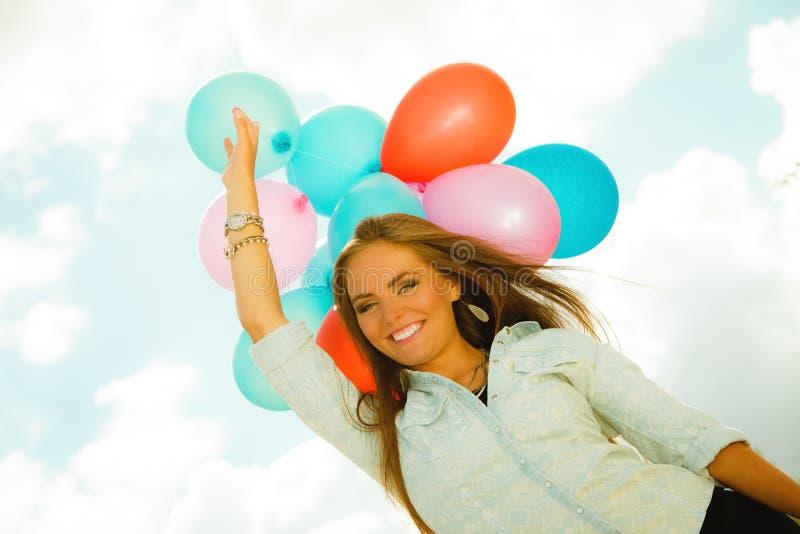 Fille heureuse avec les ballons colorés dehors photos stock