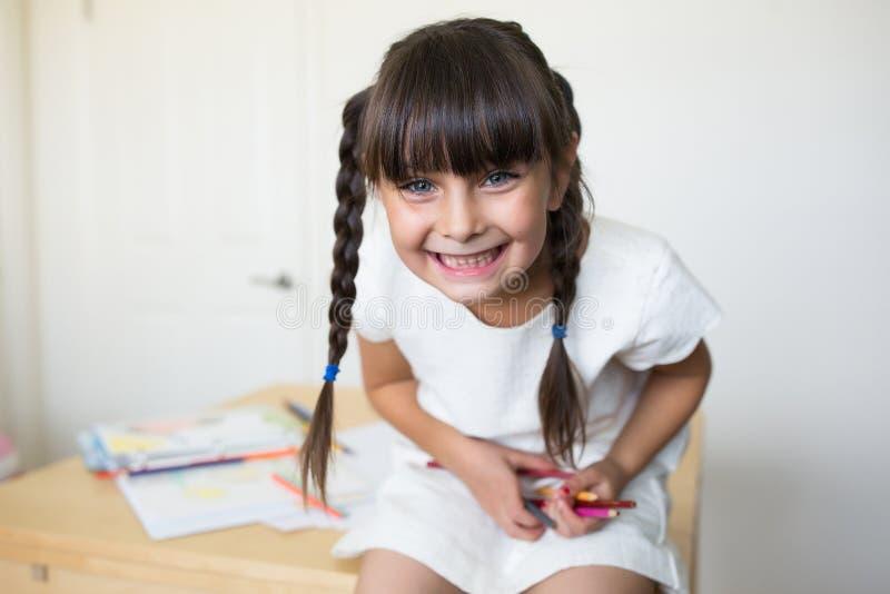 Fille heureuse avec les crayons colorés à disposition photographie stock
