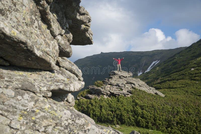 Fille heureuse avec les mains tendues se tenant sur la roche image libre de droits