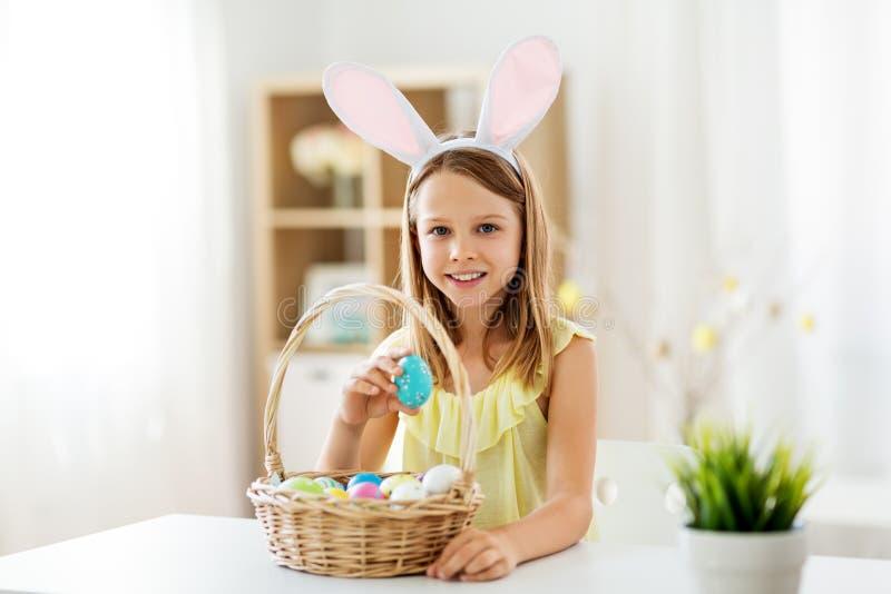 Fille heureuse avec les oeufs de pâques colorés à la maison photo libre de droits