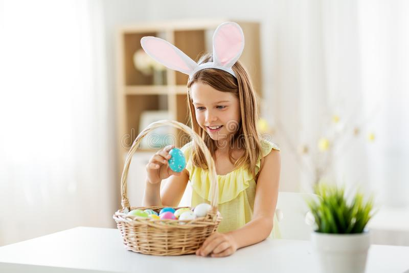 Fille heureuse avec les oeufs de pâques colorés à la maison image stock