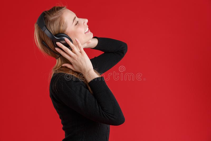 Fille heureuse, avec les yeux fermés appréciant la musique dans les écouteurs et le sourire Sur un fond rouge image libre de droits