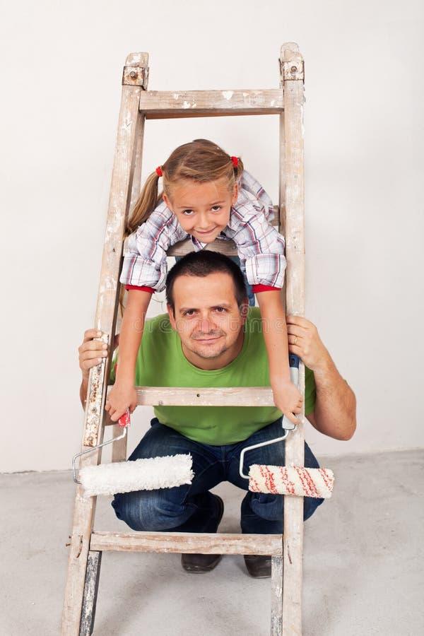 Fille heureuse avec son père peignant la salle image stock