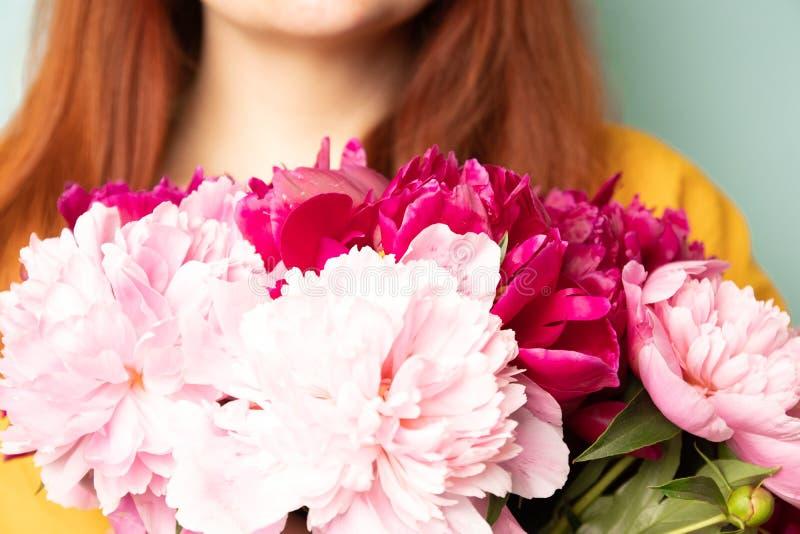 Fille heureuse avec un bouquet des pivoines sur le fond bleu-clair photographie stock libre de droits