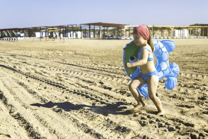 Fille heureuse avec un cercle gonflable fonctionnant le long de la plage images stock