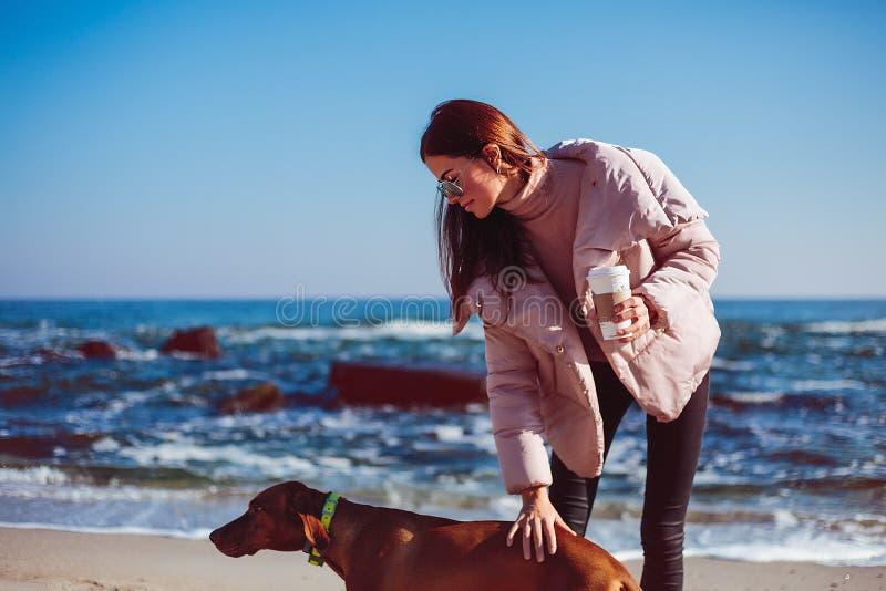 Fille heureuse avec un chien à la mer image libre de droits