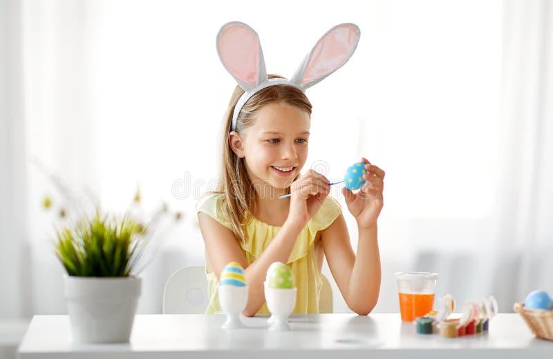 Fille heureuse colorant des oeufs de pâques à la maison photos libres de droits